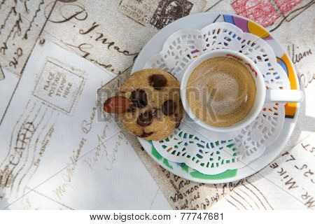 A cup of espresso and a shortcake with chocolate chips and almond nut on the letters print table cloth. Top view.