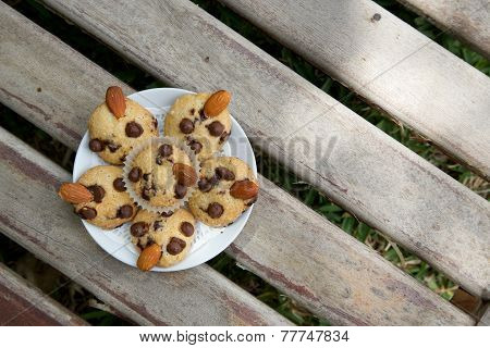 A plate of mini shortcakes with chocolate chips and almond nuts on the wooden surface. Top view