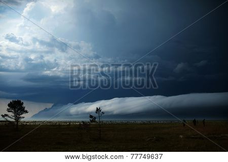 three people look at the looming clouds over the sea during a storm