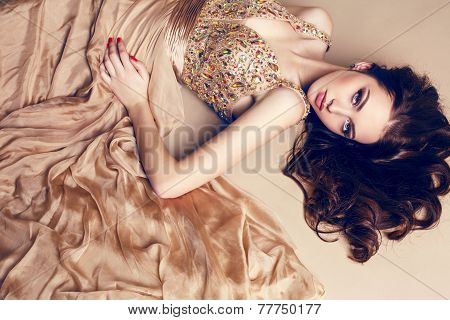 Beautiful Brunette In Luxurious Sequin Dress Posing At Studio