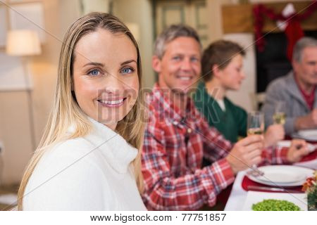 Woman smiling at camera during christmas dinner at home in the living room