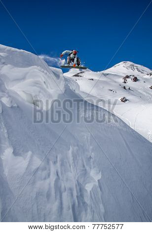 Snowboarder  jumping against blue sky  in sunny day. In backround the mt. Elbrus , Caucasus