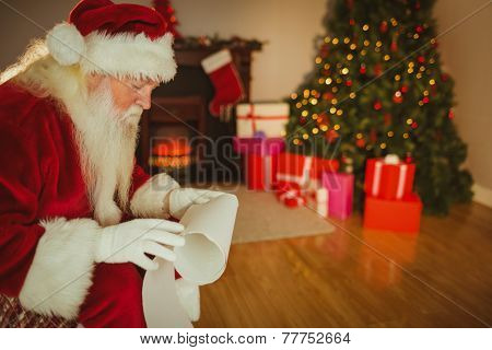 Santa claus reading his list at home in the living room