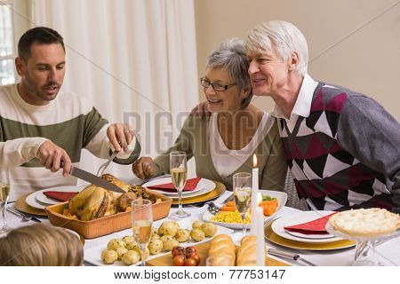 Man carving chicken during christmas dinner at home in the living room