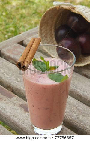 Plum yogurt in a glass on an old wooden surface