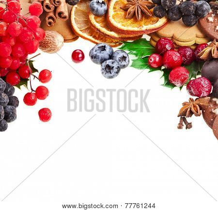border of christmas cookie , holly berries , xmas ingredients and spices on a white background