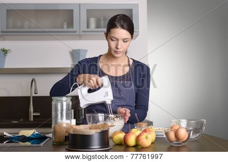 Young Woman Baking An Apple Pie In The Kitchen