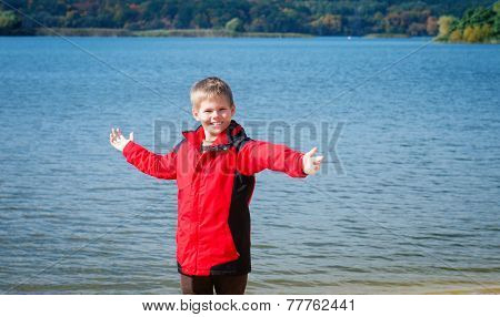 Happy Boy Near The River. Fall. Child Having Fun Outdoors. Freedom Concept.
