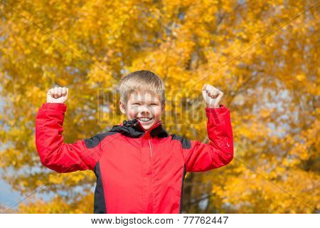 Happy Boy in Autumn Park. Fall. Child Having Fun Outdoors. Yellow Trees and Leaves. Freedom Concept.