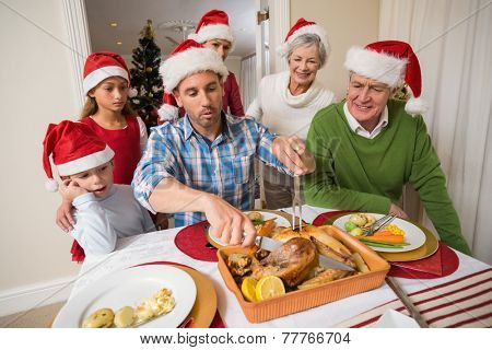 Father in santa hat carving chicken during dinner at home in the living room