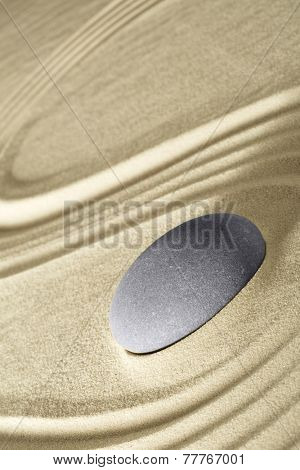Spa wellness stone for massage therapy? Zen meditation sand garden background.Treatment for relaxation and harmony in health