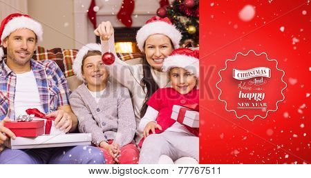Happy family wearing santa hat on the couch against red vignette