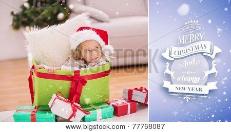 Cute little girl sitting in giant christmas gift against purple vignette