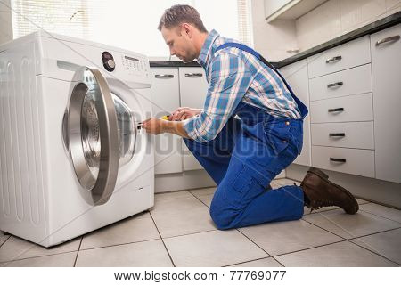 Handyman fixing a washing machine in the kitchen