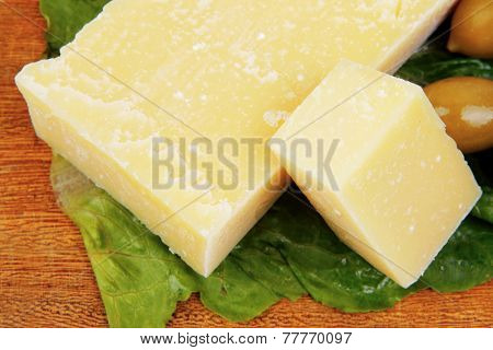 yellow edam cheese on wooden platter with olives and tomato isolated over white background