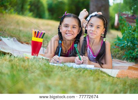Hispanic Sisters Drawing In Summer Park