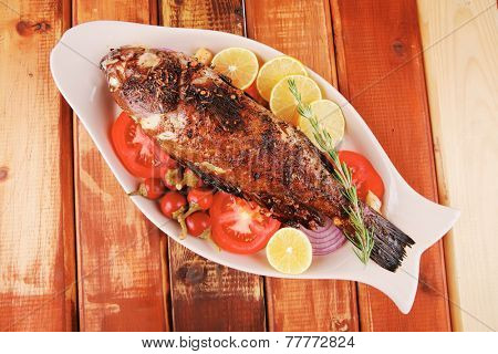 main course: whole fried sunfish on wooden table with lemons and peppers