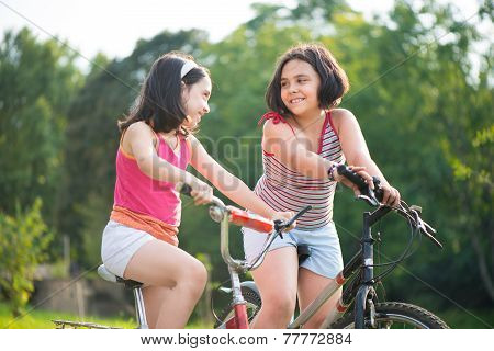 Two Hispanic Children Riding On Bikes