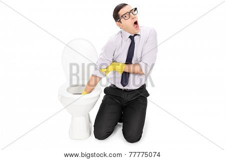 Disgusted man cleaning a toilet with cleaning gloves isolated on white background