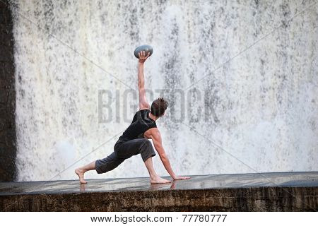 Fit white man exercising with elliptical ball  at waterfall - back view