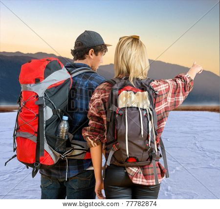 Couple of hikers witnessing a serene sunrise over the salt flats in Death Valley