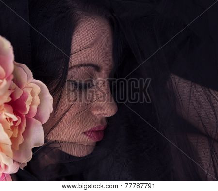 Woman with black tulle on face