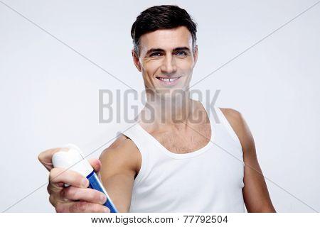 Happy man spraying deodorant over gray background