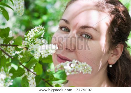 Young Woman Smelling Flower In Branch Of Tree