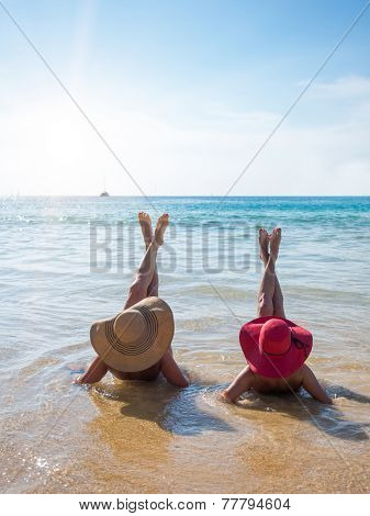 Back View of two young playful women in summer hats resting on the beach and enjoy the tropical sea.