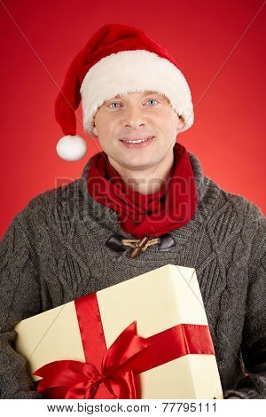 Santa man holding big giftbox tied up by red ribbon