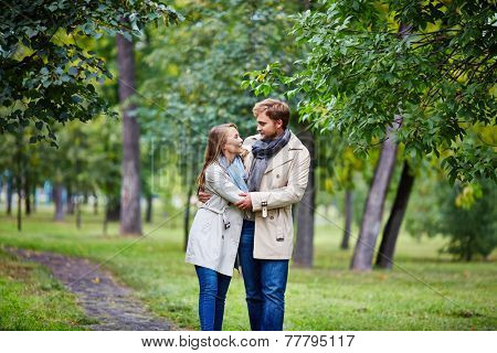Amorous man and woman spending leisure in summer park