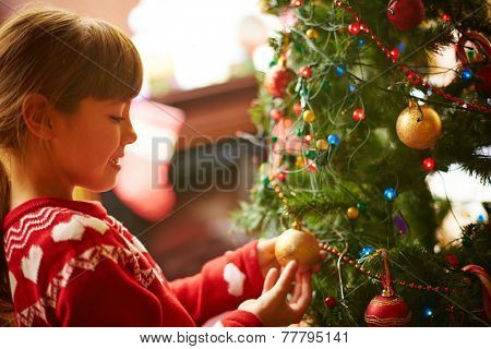 Cute little girl decorating Christmas firtree before holiday