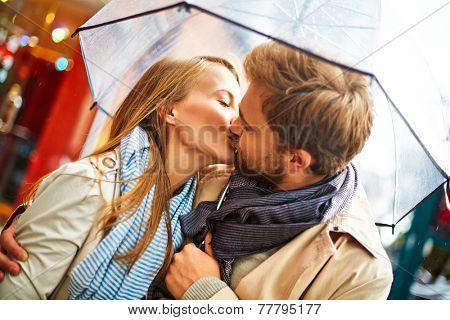 Amorous couple kissing under umbrella in urban environment