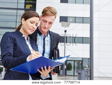 Two business people checking contract files outside in the city