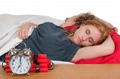 stock photo of time-bomb  - Young couple sleeping in bed with a time bomb alarm clock - JPG