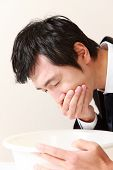 pic of vomiting  - middle aged Japanese businessman wearing suit and vomits - JPG