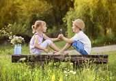 stock photo of bench  - Cute boy and girl in love - JPG