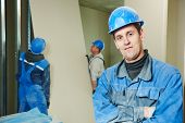 stock photo of millwright  - cheerful plasterboard workers team at a indoors wall insulation works - JPG