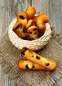 picture of baked raisin cookies  - Arrangement of Biscuit Raisin Cookies in Wicker Bowl on Sackcloth closeup on Rustic Wooden background - JPG