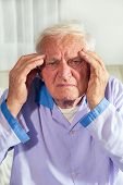 stock photo of ibuprofen  - Senior man with headache sitting on the bed - JPG