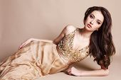 picture of studio  - fashion studio portrait of beautiful young girl with dark hair wearing luxurious beige dress - JPG