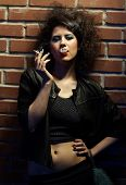 image of pimp  - portrait of girl dressed like hooker posing near brick wall - JPG