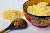 picture of millet  - millet porridge in a beautiful bowl with Khokhloma painting on a white tablecloth with scattered millet - JPG