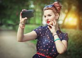 picture of fifties  - Beautiful young woman in fifties style taking picture of herself outdoor - JPG
