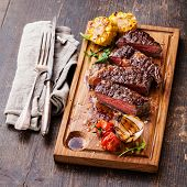 pic of ribeye steak  - Sliced medium rare grilled Beef steak Ribeye with corn and cherry tomatoes on cutting board on wooden background - JPG