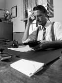 stock photo of 1950s style  - Depressed businessman sitting at desk and holding a gun 1950s style office - JPG