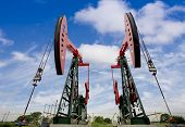 foto of derrick  - Working oil pump jacks on a oil field - JPG