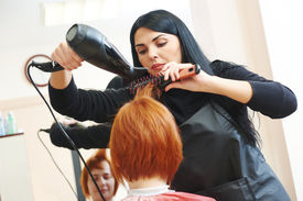 stock photo of beauty parlour  - hairdresser drying hair with blow dryer of woman client at beauty parlour after highlighting - JPG