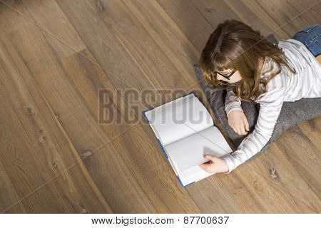 High angle view of teenage girl reading book on floor at home