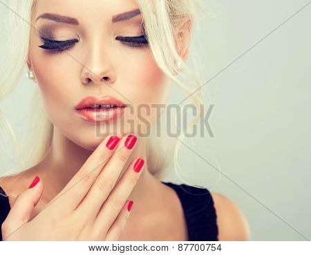 Beautiful blonde woman with retro hairstyle and red nail manicure